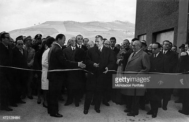 'Italian President of the Council of Ministers Aldo Moro cutting the inauguration ribbon at Mondadori paper factory beside Italian publisher Arnoldo...