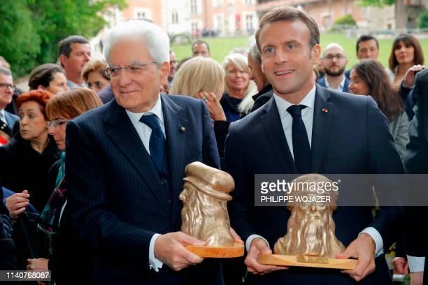 TOPSHOT Italian President Sergio Mattarella and French President Emmanuel Macron hold busts of Italian renaissance painter and scientist Leonardo da...