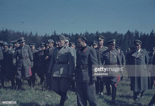 Italian Prime Minister Benito Mussolini walks with Italian and German officers and troops assigned to the Eastern Front during the invasion of the...