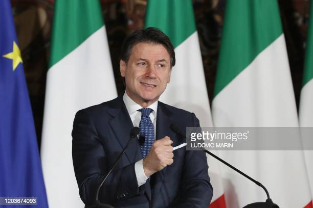 Italian Prime Minister Giuseppe Conte gestures as he takes part in a press conference with the French President during a Franco-Italian summit at the...
