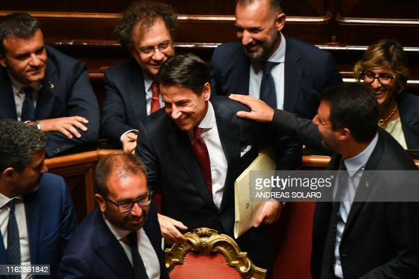 Italian Prime Minister Giuseppe Conte reacts as Interior Minster Matteo Salvini touches his shoulder upon his arrival to deliver a speech at the...