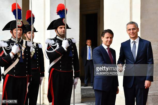 Italian Prime Minister Giuseppe Conte shakes hands as he welcomes NATO General Secretary Jens Stoltenberg next to carabinieri members of the Honor...