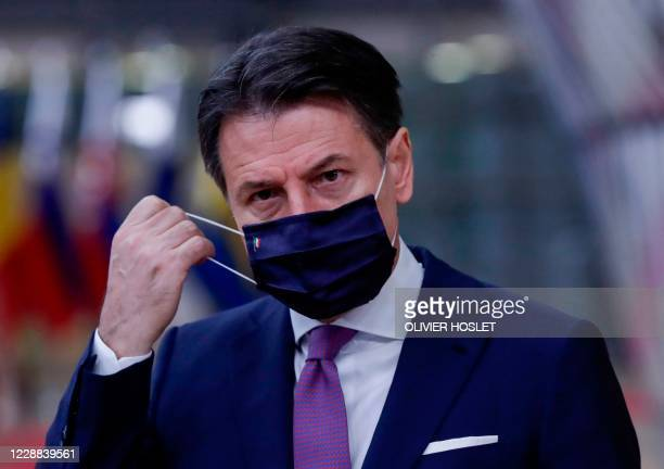 Italian Prime Minister Giuseppe Conte takes off his mask as he arrives on the second day of a European Union summit at The European Council Building...