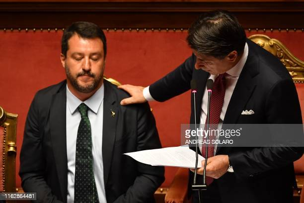 TOPSHOT Italian Prime Minister Giuseppe Conte touches Deputy Prime Minister and Interior Minister Matteo Salvini's shoulder as he delivers a speech...