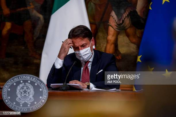 Italian Prime Minister Giuseppe Conte wearing a protective mask holds a press conference after the Cabinet for the decree law August at Palazzo Chigi...