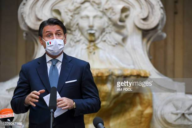 Italian Prime Minister Giuseppe Conte wearing a protective mask holds a press conference on the new safety measures to contain the Covid-19 pandemic,...