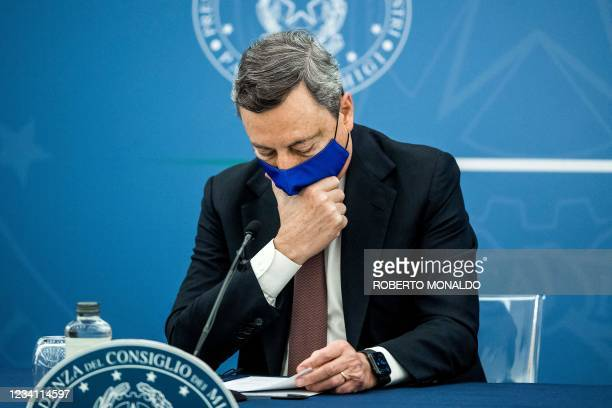 Italian Prime Minister Mario Draghi touches his face mask during a press conference with Italy's Justice Minister and Italy's Health Minister at the...