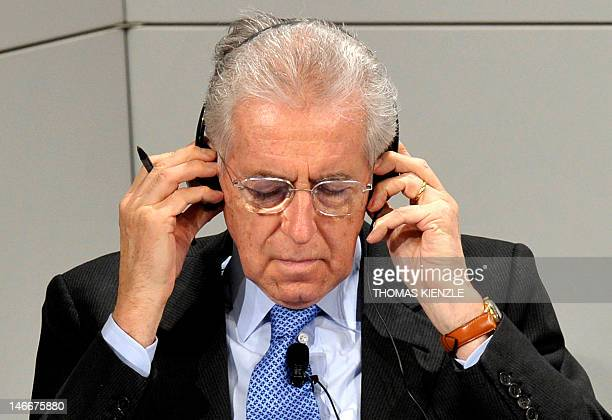 Italian Prime Minister Mario Monti arranges his headphones during the 48th Munich Security Conference at the Bayerischer Hof hotel in Munich southern...
