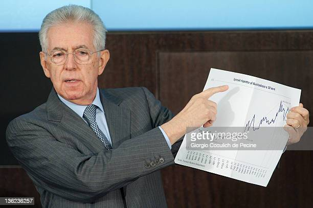 Italian Prime Minister Mario Monti shows a graph illustrating the spread of between Italian and German bonds during an end-of-year press conference...