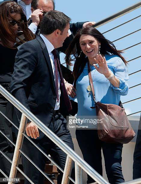 Italian Prime Minister Matteo Renzi helps Italy's Democratic Party's MEP Pina Picierno who is pregnant after she slipped during the visit to the port...
