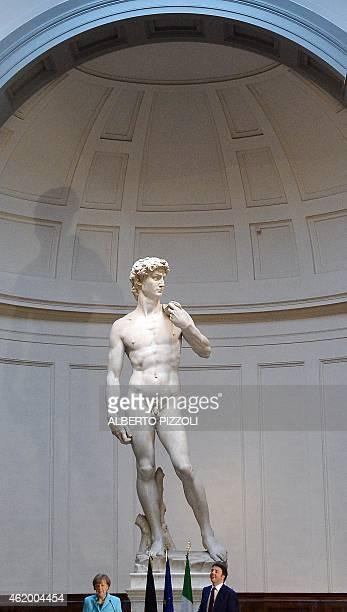 Italian Prime Minister Matteo Renzi speaks flanked by German Chancellor Angela Merkel beneath the original 16th century statue of David by Italian...