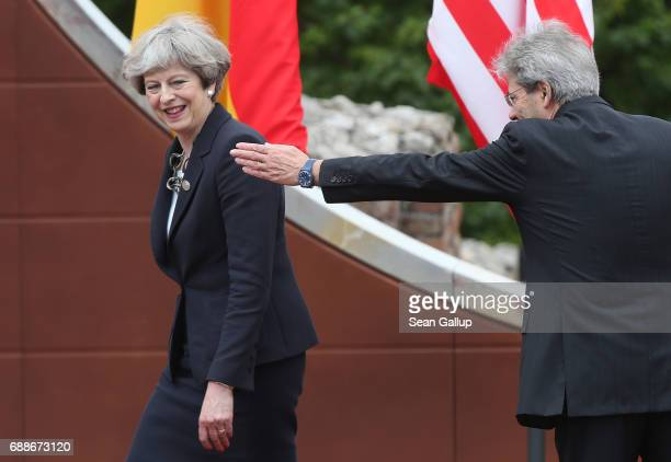 Italian Prime Minister Paolo Gentiloni gestures ro show British Prime Minister Theresa May where to go in the ancient amphiteater at the G7 Taormina...