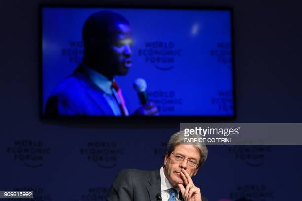 Italian Prime Minister Paolo Gentiloni listen a refugee seen on the TV screen behind during a session on mass migration across the Mediterranean...