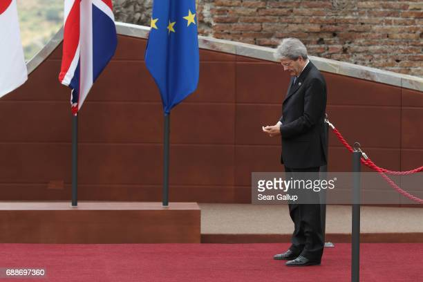 Italian Prime Minister Paolo Gentiloni looks at a mobile phone as he waits for other G7 leaders to arrive in the ancient amphiteater at the G7...