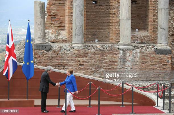 Italian Prime Minister Paolo Gentiloni welcomes German Chancellor Angela Merkel in the ancient amphiteater at the G7 Taormina summit on the island of...