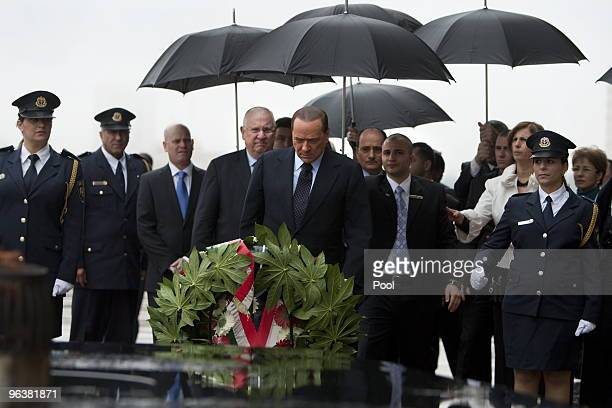 Italian Prime Minister Silvio Berlusconi accompanied by Israel's Speaker of the Parliament Reuven Rivlin pays his respects at the memorial for fallen...