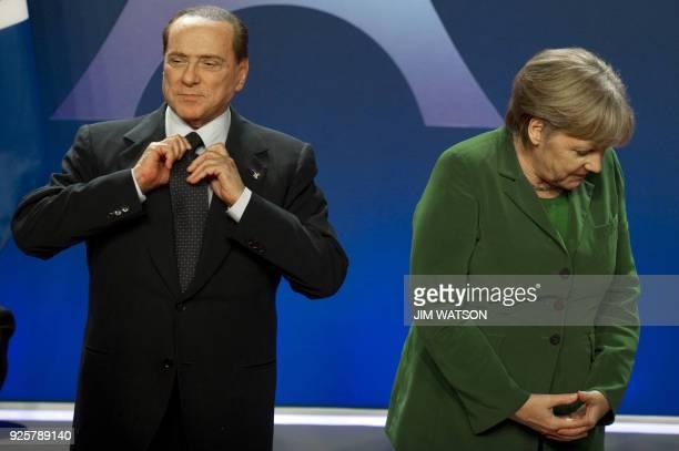 Italian Prime Minister Silvio Berlusconi adjusts his tie next to German Chancellor Angela Merkel before posing for a family photo on November 3 2011...