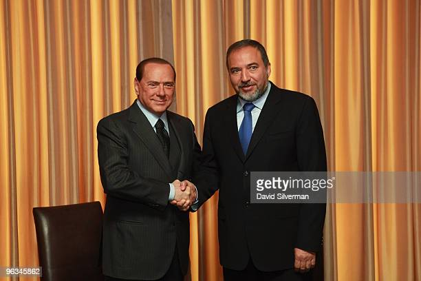 Italian Prime Minister Silvio Berlusconi and Israeli Foreign Minister Avigdor Lieberman shake hands during a media opportunity at the start of their...