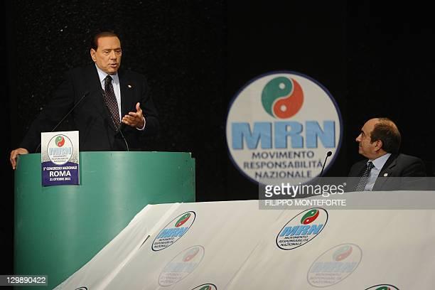 """Italian Prime Minister Silvio Berlusconi delivers a speech on stage with Domenico Scilipoti, the general secretary of the new party MRN """"Movimento..."""