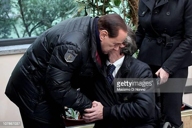 Italian Prime Minister Silvio Berlusconi embraces Alberto Torregiani, the son of Pierluigi Torregiani during a press conference at Linate military...