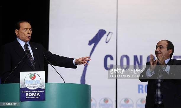 "Italian Prime Minister Silvio Berlusconi is applauded on stage by Domenico Scilipoti, the general secretary of the new party MRN ""Movimento..."