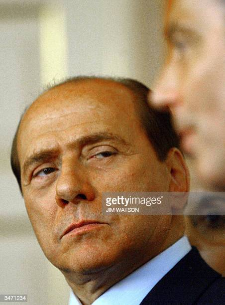 Italian Prime Minister Silvio Berlusconi looks at British Prime Minister Tony Blair during a press conference inside No 10 Downing Street in London...