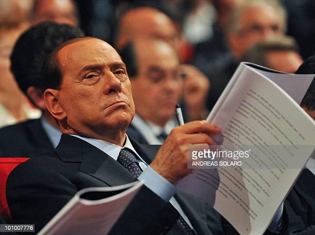 Italian Prime Minister Silvio Berlusconi looks on as the head of the Italian employers group, the Confindustria, Emma Marcegaglia delivers a speech...