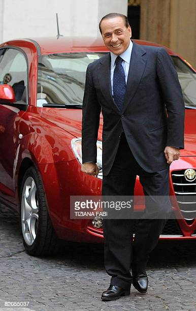 Italian Prime Minister Silvio Berlusconi poses next to the new Alfa Romeo Mito during the official presentation at Palazzo Chigi in Rome on July 24...