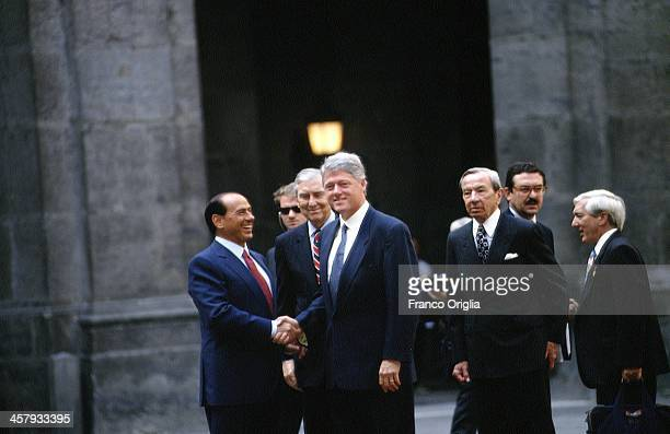 Italian Prime Minister Silvio Berlusconi shakes hands with 42nd President of the United States Bill Clinton on the right US Secretary of State Warren...