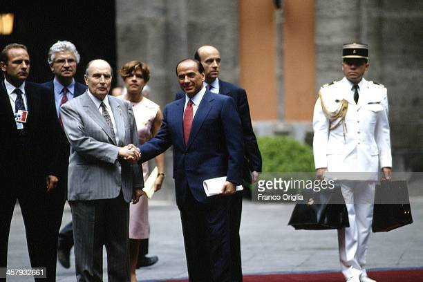 Italian Prime Minister Silvio Berlusconi shakes hands with French President Francois Mitterrand in the background French Foreign Minister Alain Juppe...