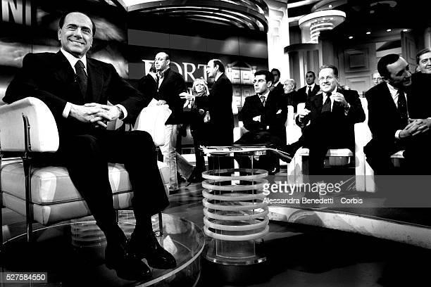 Italian Prime Minister Silvio Berlusconi smiles as he prepares to participate in a political talk show at the Italian TV channel RAI's broadcast...