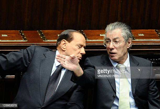 Italian Prime Minister Silvio Berlusconi talks with Reforme Minister Umberto Bossi upon arrival at the Chamber of Deputies in Rome on September 22,...