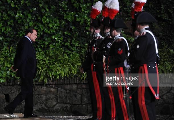 Italian Prime Minister Silvio Berlusconi walks as he waits for the arrival of Kazakhstan president Nursultan Nazarbayev prior their meeting on...