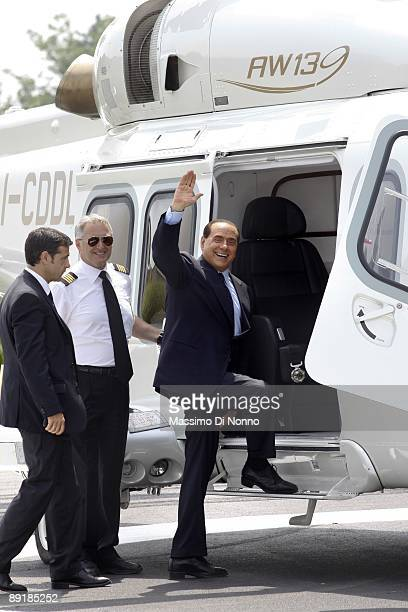 Italian Prime Minister Silvio Berlusconi waves as he prepares to depart by helicopter after attending the opening of the construction site for the...
