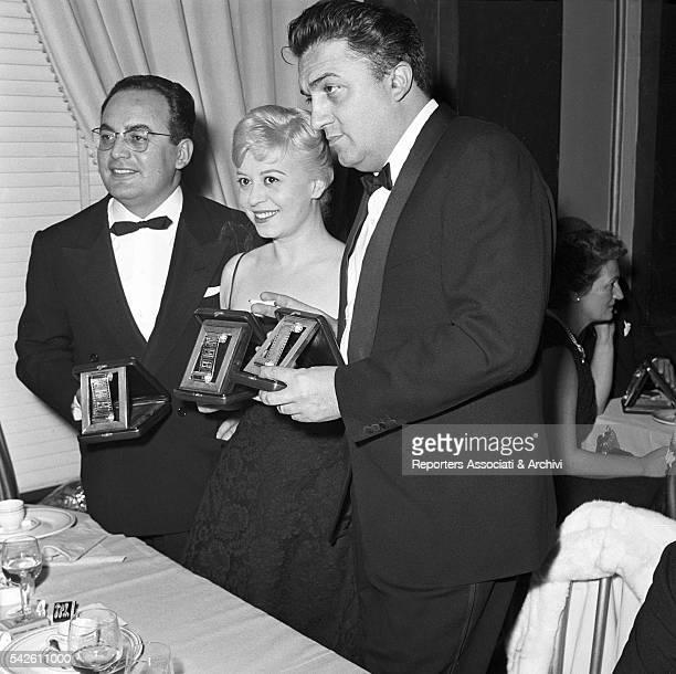 Italian producer Dino De Laurentiis Italian director Federico Fellini and Italian actress Giulietta Masina at the Silver Ribbons prize ceremony 1958