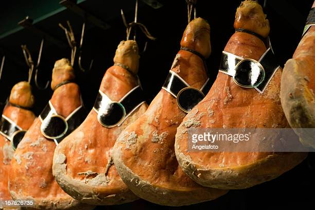italian prosciutto hanging in line - prosciutto stock photos and pictures
