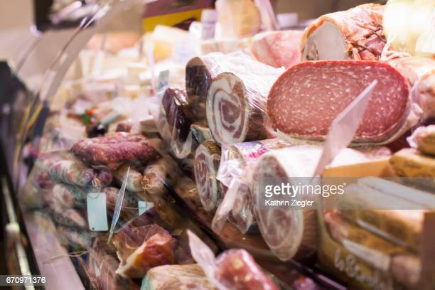 Italian prosciutto, salami and cheese in display cabinet at delicatessen, Naples, Italy