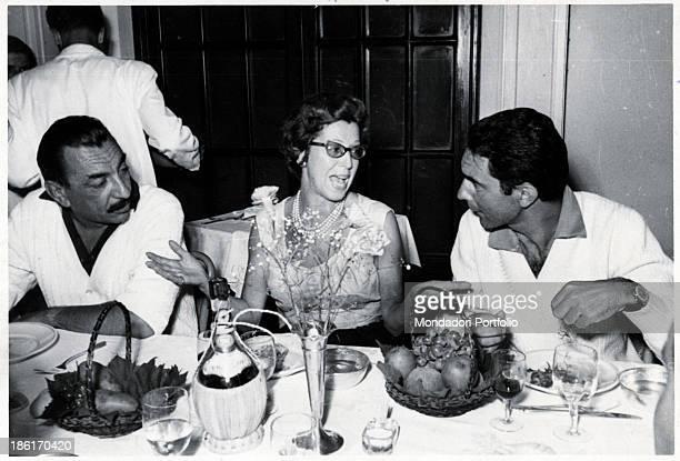 Italian publisher Alberto Mondadori sitting at a table with Italian journalist and writer Italo Calvino and Albertina Antonelli wife of Italian...