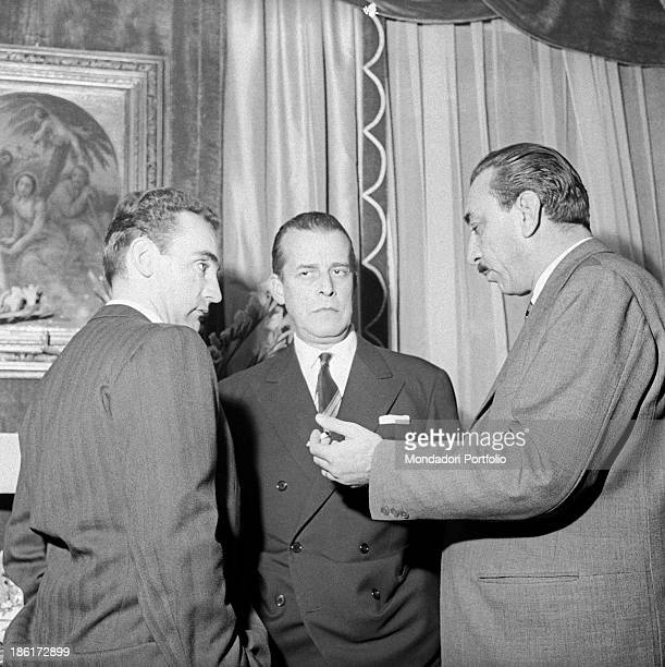 Italian publisher Alberto Mondadori talking to two men at the party in honour of German writer Alfred Andersch and French writer Michel Butor Milan...