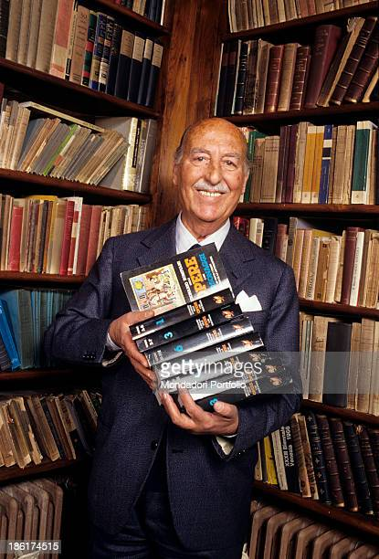 Italian publisher and playwright Valentino Bompiani executive of the review Sipario in his library holds in his hands a few volumes of Dizionario...