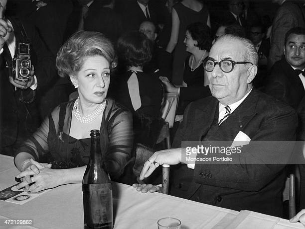 Italian publisher Arnoldo Mondadori sitting at the table with Italian actress Andreina Pagnani They attended the Cassaforte d'Oro awarding ceremony...