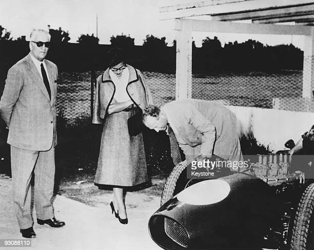 Italian race car driver and businessman Enzo Ferrari gives the former King Leopold and Princess Lilian of Belgium a tour of the Ferrari plant in...
