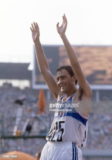 Italian race walker Maurizio Damilano raises his arms in the air in celebration after crossing the finish line in first place to win the gold medal...