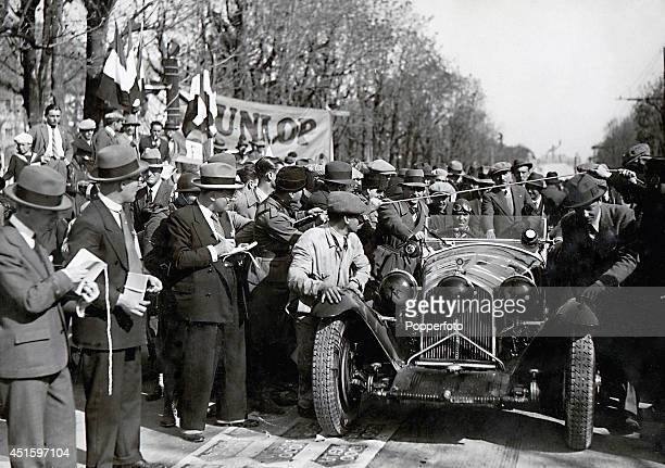 Italian racing car driver Tazio Nuvolari being pushed to the start of the Mille Miglia in his Tipo 8C 2300 Alfa Romeo assisted by his...