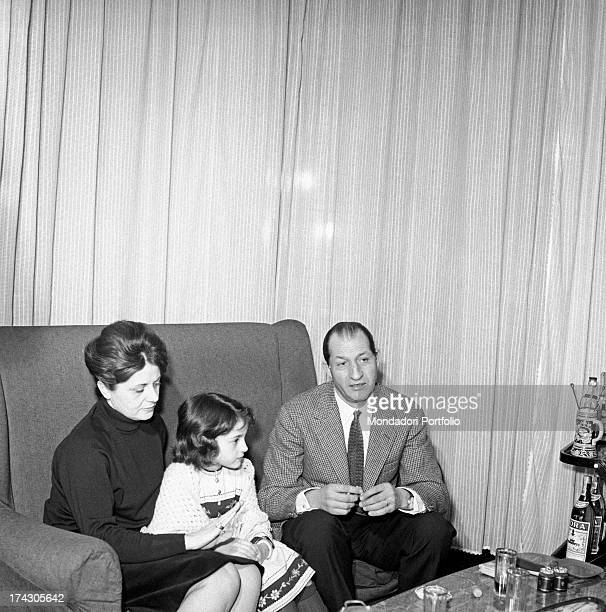 Italian racing cyclist Gino Bartali, his wife Adriana Bani and their daughter Bianca Maria Bartali sitting on the sofa. Florence, 1960s.
