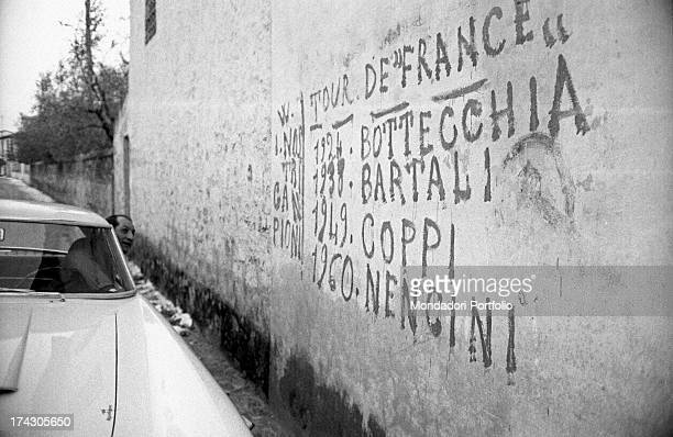 Italian racing cyclist Gino Bartali leaning out of the car window to watch the graffitis on a wall reminding the Italian winners of the Tour de...