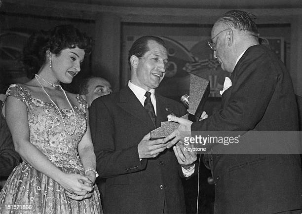 Italian racing cyclist Gino Bartali receives the sports journalists' 'Golden Saddle' award at the Teatro Odeon Milan 25th March 1955 On the left is...