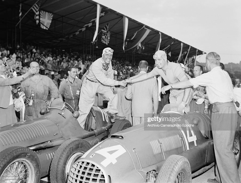 Italian racing driver Giuseppe Farina (1906 - 1966, left) shakes hands with Alberto Ascari (1918 - 1955) at the Lausanne Grand Prix in Switzerland, 27th August 1949.