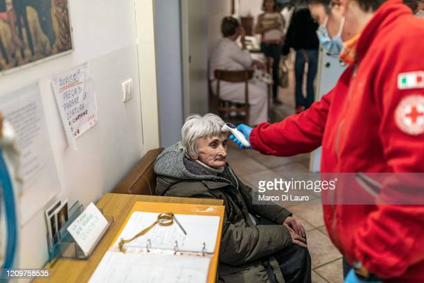 Italian Red Cross member Beatrice Rossi takes the temperature of an elderly homeless woman to check that she is not positive for COVID19 before her...