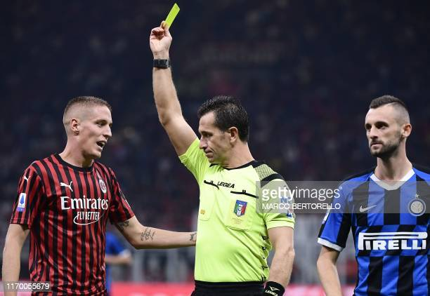 Italian referee Daniele Doveri gives a yellow card to AC Milan's Italian defender Andrea Conti as Inter Milan's Croatian defender Marcelo Brozovic...